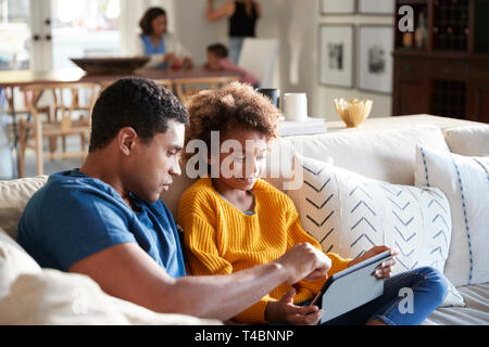 Pre-teen girl sitting on sofa in the living room using tablet computer with her father, mother and toddler sitting at a table in the background, selective focus