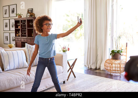 Pre-teen girl filming herself singing using a social media app on her smartphone - Stock Photo