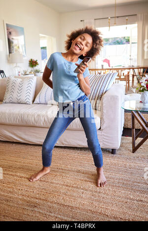 Pre-teen black girl singing and dancing in the living room, using a social media app on her smartphone, full length, vertical - Stock Photo