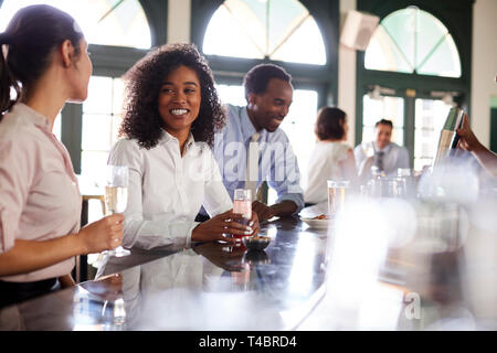 Two Businesswomen Meeting For After Works Drinks In Bar - Stock Photo