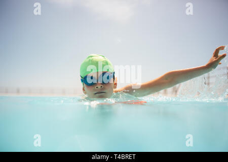 Boy with swim cap and goggles practice swimming in outdoor pool. Boy learning to swim on summer day. - Stock Photo