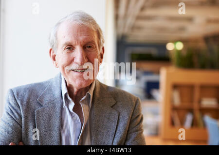 Portrait Of Smiling Senior Businessman In Modern Office Standing By Window - Stock Photo
