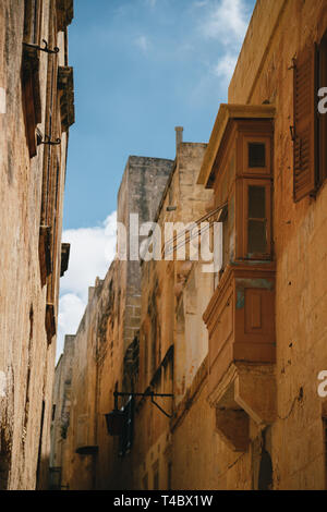 Yellow narrow medieval street with typical maltese balcony in Mdina, ancient capital of Malta, fortified medieval town. Popular touristic destination - Stock Photo