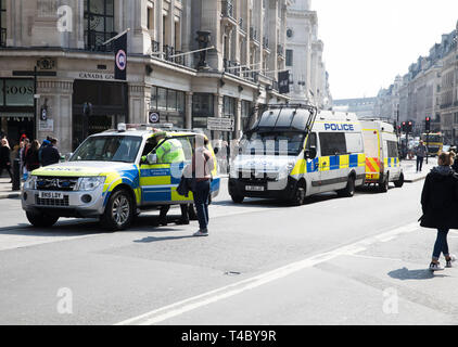 London, UK. 15th Apr, 2019. Climate change protesters In Oxford Circus and Regent street as Environmental protesters paralyse London's roads by creating human barricades at five landmarks. Extinction Rebellion organisers claim 30,000 eco-protesters are expected to block major routes today. They also pulled a boat up Regent Street to highlight the threat of Global Warming, but on a darker side they smashed windows at Shells headquarters. Credit: Keith Larby/Alamy Live News - Stock Photo