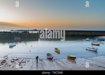 Mousehole, Cornwall, UK. 16th Apr, 2019. UK Weather. After 3 days of gale force winds and heavy rain, the weather has swung round this morning ahead of the Easter weekend. It was calm and mild at sunrise with the promise of a hot day ahead. This photographer was out in the harbour photographing the small fishing boats at sunrise. Credit: Simon Maycock/Alamy Live News - Stock Photo