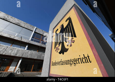16 April 2019, Baden-Wuerttemberg, Karlsruhe: A sign with a federal eagle and the words 'Bundesverfassungsgericht' (Federal Constitutional Court), taken before the court in Karlsruhe. The Second Senate of the court is negotiating the euthanasia ban. Euthanasia as a service has been a punishable offence for a good three years now. The court is hearing a number of lawsuits against the ban. With Section 217 of the Criminal Code, the legislator wanted to prevent suicide assistance associations such as Sterbehilfe Deutschland or Dignitas from Switzerland from expanding their services for paying mem - Stock Photo