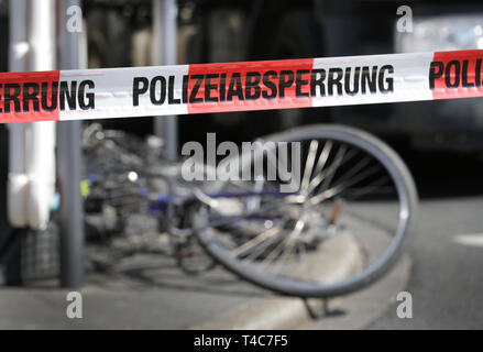 16 April 2019, North Rhine-Westphalia, Düsseldorf: Behind a barrier tape with the inscription 'Police barrier', a bicycle is lying in front of a truck at the scene of the accident. There has been an accident with a truck (in the back) and a cyclist in downtown Düsseldorf. More precise circumstances regarding the cause of the accident are not yet known. Photo: Martin Gerten/dpa - Stock Photo