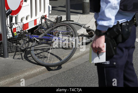 16 April 2019, North Rhine-Westphalia, Düsseldorf: A police officer is standing in front of a bicycle at the scene of the accident. There has been an accident with a truck (in the back) and a cyclist in downtown Düsseldorf. More precise circumstances regarding the cause of the accident are not yet known. Photo: Martin Gerten/dpa - Stock Photo