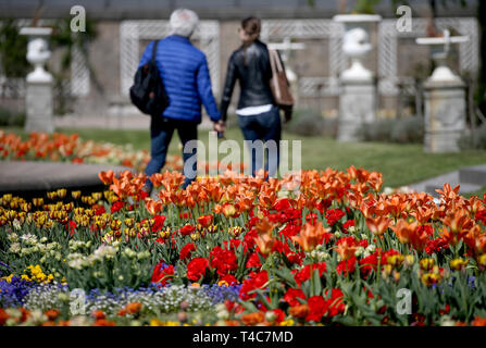 16 April 2019, North Rhine-Westphalia, Köln: A couple walks along a flower bed in the flora. Photo: Oliver Berg/dpa - Stock Photo