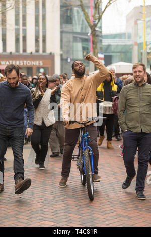 Birmingham, UK. 16th April, 2019. A diverse team of one hundred community actors, musicians and stewards alongside Saltine Theatre Company re-tell the Easter story in a live procession through Birmingham city centre. Christ is riding into the city on a bicycle. The procession finishes up at St. Philip's Cathedral.  Peter Lopeman/Alamy Live News - Stock Photo