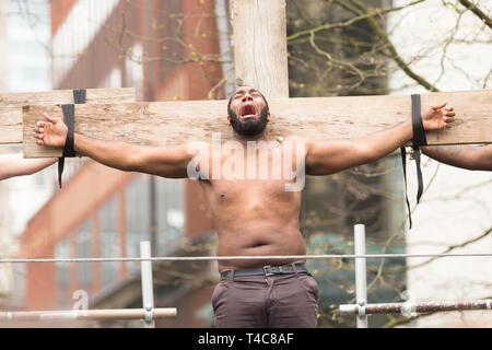 Birmingham, UK. 16th April, 2019. A contemporary Christ-figure is crucified. A diverse team of one hundred community actors, musicians and stewards alongside Saltine Theatre Company re-tell the Easter story in a live procession through Birmingham city centre. The procession finishes up at St. Philip's Cathedral  Peter Lopeman/Alamy Live News - Stock Photo