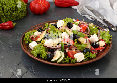 Healthy salad of lettuce, tomato, red onion, pepper, soft cheese, olives, basil, cucumbers, with olive oil and lemon juice. Greek salad - Stock Photo