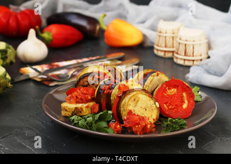 Ratatouille with baked vegetables: aubergines, zucchini and tomatoes is located on a plate on a dark background, On the table there are cutlery, salt, - Stock Photo