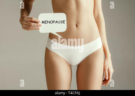 Handwriting text writing Menopause. Concept meaning cessation of menstruation. Young adult woman holding paper card for sign or symbol. Cut out part of body. Medical problem and solution. - Stock Photo