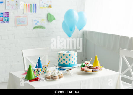 festive cake and party caps on table in room decorated for birthday party with air balloons - Stock Photo