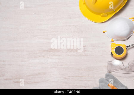 Construction site safety. Protective hard hat, gloves, glasses and masks on wooden background, copy space, top view - Stock Photo