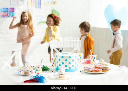 kids having fun during birthday party near table with cake, donuts and cupcakes at home - Stock Photo