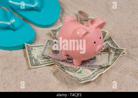 Horizontal shot of a pair of blue flip-flops and a pink piggy bank sitting on a pile of money with money in its slot on a sand beach. - Stock Photo