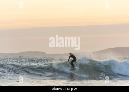 Tenby, Pembrokeshire/UK.04.18.2018-Surfer riding the wave in rough sea at sunset.Healthy, active lifestyle, extreme sport.Recreational pursuit. - Stock Photo