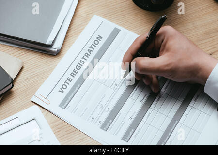 cropped view of man filling in Vote Registration Election Concept - Stock Photo