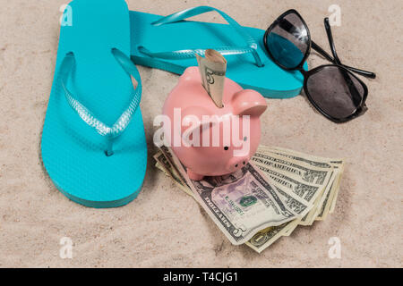 Horizontal shot of a pair of blue flip-flops and a pink piggy bank sitting on a pile of money with money in its slot on a sand beach background. There - Stock Photo