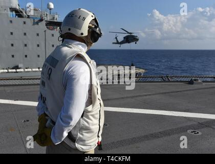 SOUTH CHINA SEA (March 20, 2019) - Chief Boatswain's Mate Jose Mendoza, from Manila, Philippines, stands by to receive supplies from a MH-60S Sea Hawk helicopter attached to the Golden Falcons of Helicopter Sea Combat Squadron 12 during a vertical replenishment between Fleet Replenishment Oiler USNS Guadalupe (T-AO 200) and U.S. 7th Fleet Flagship USS Blue Ridge (LCC 19). Blue Ridge is the oldest operational ship in the Navy and, as 7th Fleet command ship, actively works to foster relationships with allies and partners in the Indo-Pacific Region. - Stock Photo