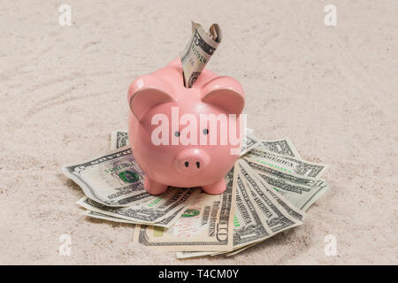 Horizontal shot of a piggy bank with cash on a sandy vacation beach. - Stock Photo