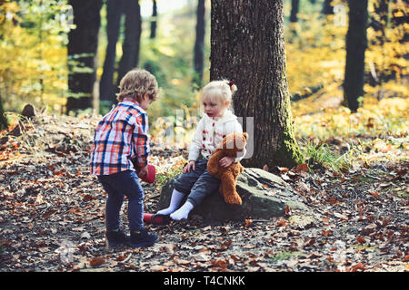 Brother help sister to put red boots. Little boy put shoes on girl feet. Helping hand concept. Children getting ready for walk in autumn forest - Stock Photo