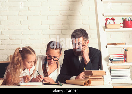 School time of girl sisters with father. Father helps children to study at home. Back to school and home schooling. Teacher man and small girls - Stock Photo