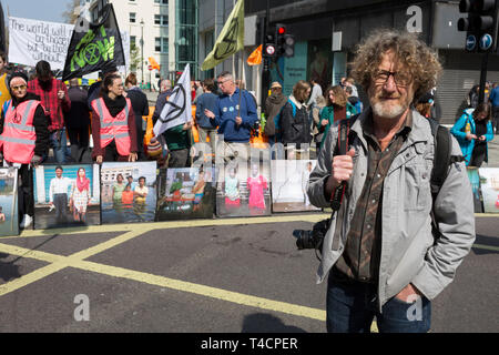 Photographer Gideon Mendel and some of his flood victim portraits 'Drowning World' during the climate Change protest with Extinction Rebellion blocking Oxford Street and simultaneously stop traffic across central London including Marble Arch, Piccadilly Circus, Waterloo Bridge and roads around Parliament Square, on 15th April 2019, in London, England. - Stock Photo