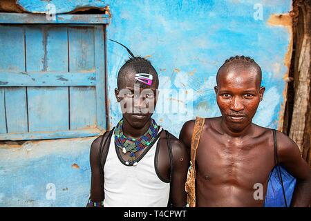 Young men of the Hamer ethnic group with colourful hair clips and pearl jewellery, Dimeka, Lower Omo Valley, Omo region, South Ethiopia, Ethiopia - Stock Photo