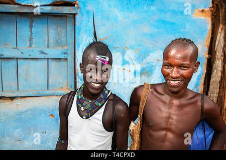 Laughing young men of the Hamer ethnic group with colorful hair clips and pearl jewelry, Dimeka, Lower Omo Valley, Omo region, South Ethiopia - Stock Photo