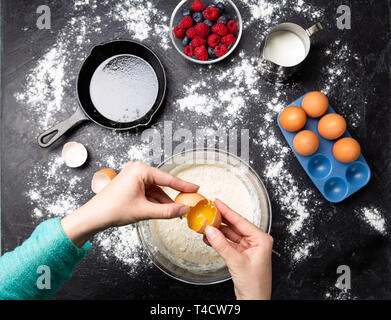 Photo of hands of man breaking eggs in bowl. Ingredients for pancakes. - Stock Photo