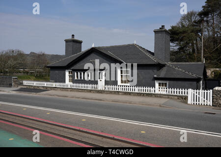 Welsh slate covered house with white picket fence,and railway lines in road in foreground in Porthmadog north wales uk - Stock Photo