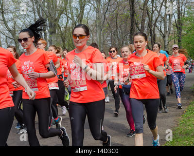 Huge group of women in orange t-shirts with numbers run marathon in the park in spring. Wroclaw, Poland - April 7, 2019. - Stock Photo
