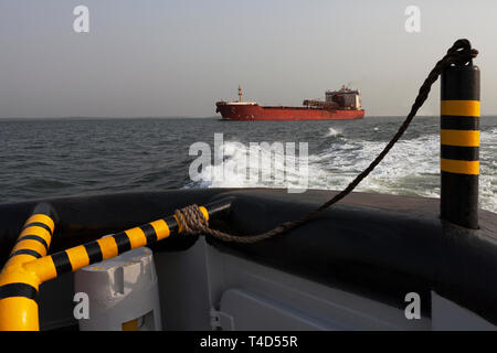 Port operations for managing & transporting iron ore. Tug escorting TGV transhipper in navigation channel to unload fines into OGV ocean going vessel - Stock Photo