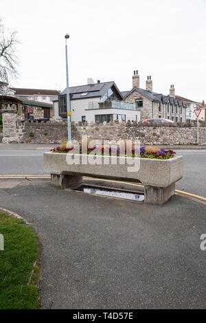 Traditional stone horse trough adjacent to a road in Rhos on Sea, North Wales, now utilised as a container for displaying flowers. - Stock Photo