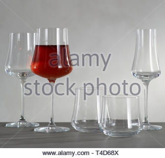 A glass of red wine and four empty wine glasses, Santino Wine Glasses, Wine glass in front of fireplace - Stock Photo