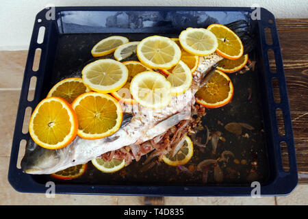 Prepared for  baking fish. Сarp filled with onions and walnutsand covered with slices of lemon and orange. Delicious homemade food. - Stock Photo