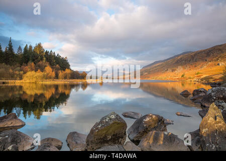 Moody, scenic view of Snowdon Horseshoe mountains at sunrise, in clouds reflected in still water of Llynnau Mymbyr, Snowdonia National Park, Wales UK.