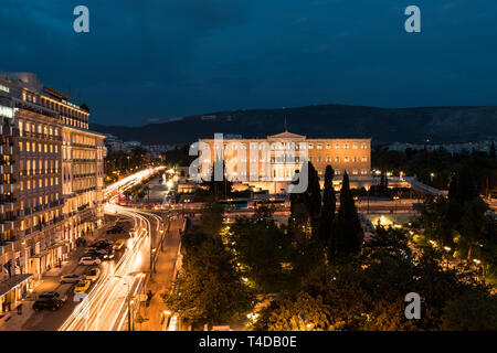 Athenian Syntagma square with the national Greek parliament building as seen by night from a lookout with traffic (Athens, Greece, Europe) - Stock Photo