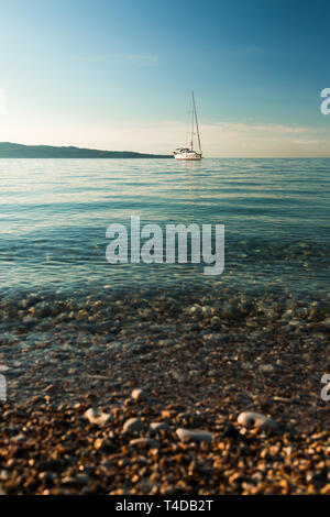 Sailing boat on a clear blue morning in the Ionian sea at a rocky beach on Corfu with clear blue water (Corfu, Greece, Europe) - Stock Photo