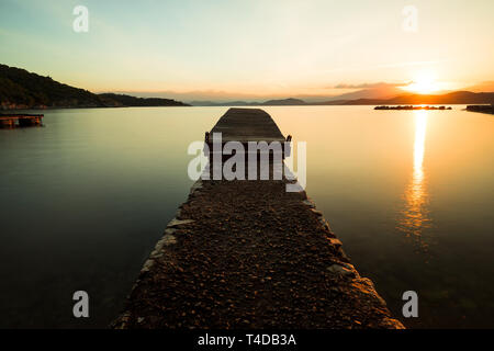 Sunrise over a little wooden pier in calm water with yellow tones, rising sun and majestic mountains (Kalami, Corfu, Greece, Europe) - Stock Photo