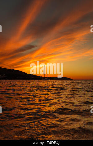 Dramatic red and orange sunset over the sea with mountain range background and yacht on the water (Kassiopi, Corfu, Greece, Europe) - Stock Photo