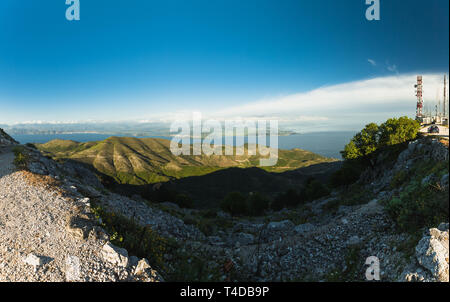 Panoramic view from the top of Mount Pantokrator, the highest mountain of Corfu with clear blue sky during evening (Corfu, Greece, Europe) - Stock Photo