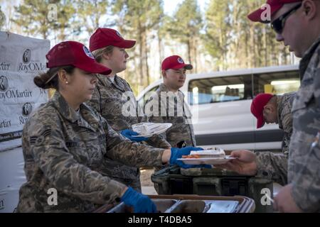 Senior Airman Caitlin Caudill, Senior Airman Hanah Hostetler, Staff Sgt. Tiger Hsu, Services members of the Ohio Air National Guard, 200th RED HORSE Squadron, prepare and serve meals as they are deployed for an Innovation Readiness Training project at Camp Kamassa, Crystal Springs, MS., helping to build a specialized camp for children with special needs, Mar. 21, 2019. IRT projects support the community while providing valuable training for the RED HORSE mission to provide a dedicated, mobile, flexible, self-sufficient heavy construction engineering force for airfield, base infrastructure and  - Stock Photo