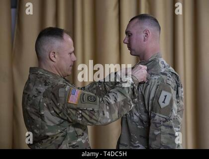 Brig. Gen. Christopher C. LaNeve, commanding general for the 7th Army Training Command, pins the Expert Infantryman Badge (EIB) on Staff Sgt. Brett Alexander, a platoon sergeant with the 1st Battalion, 16th Infantry Regiment, 1st Armored Brigade Combat Team, 1st Infantry Division, at the Vilseck Army Airfield, Rose Barracks, Germany, March 22, 2019. - Stock Photo