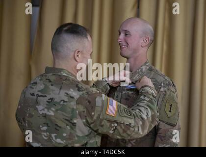 Brig. Gen. Christopher C. LaNeve, commanding general for the 7th Army Training Command pins the Expert Infantryman Badge (EIB) on Staff Sgt. Robinson Alexander, a team leader with the 1st Battalion, 16th Infantry Regiment, 1st Armored Brigade Combat Team, 1st Infantry Division, at the Vilseck Army Airfield, Rose Barracks, Germany, March 22, 2019. - Stock Photo