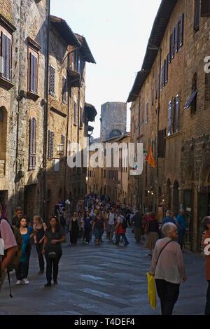 Crowds throng the Via San Giovanni, San Gimignano, Tuscany, Italy - Stock Photo