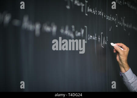 Math teacher by the blackboard during mathclass - detail of the hand with chalk - Stock Photo